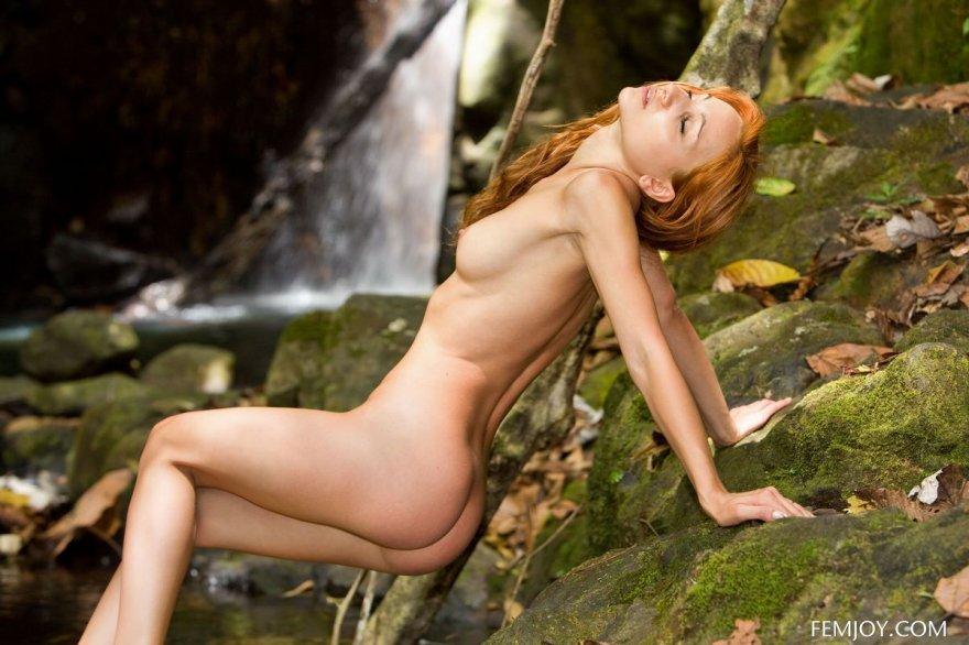 Тощая рыженькая на фоне водопада