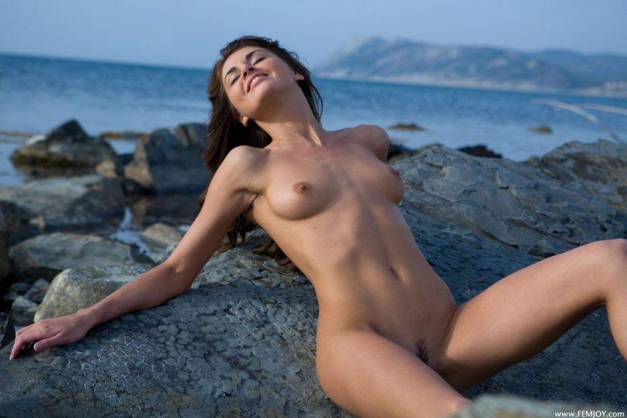 Стройная голая шатенка на камнях у моря