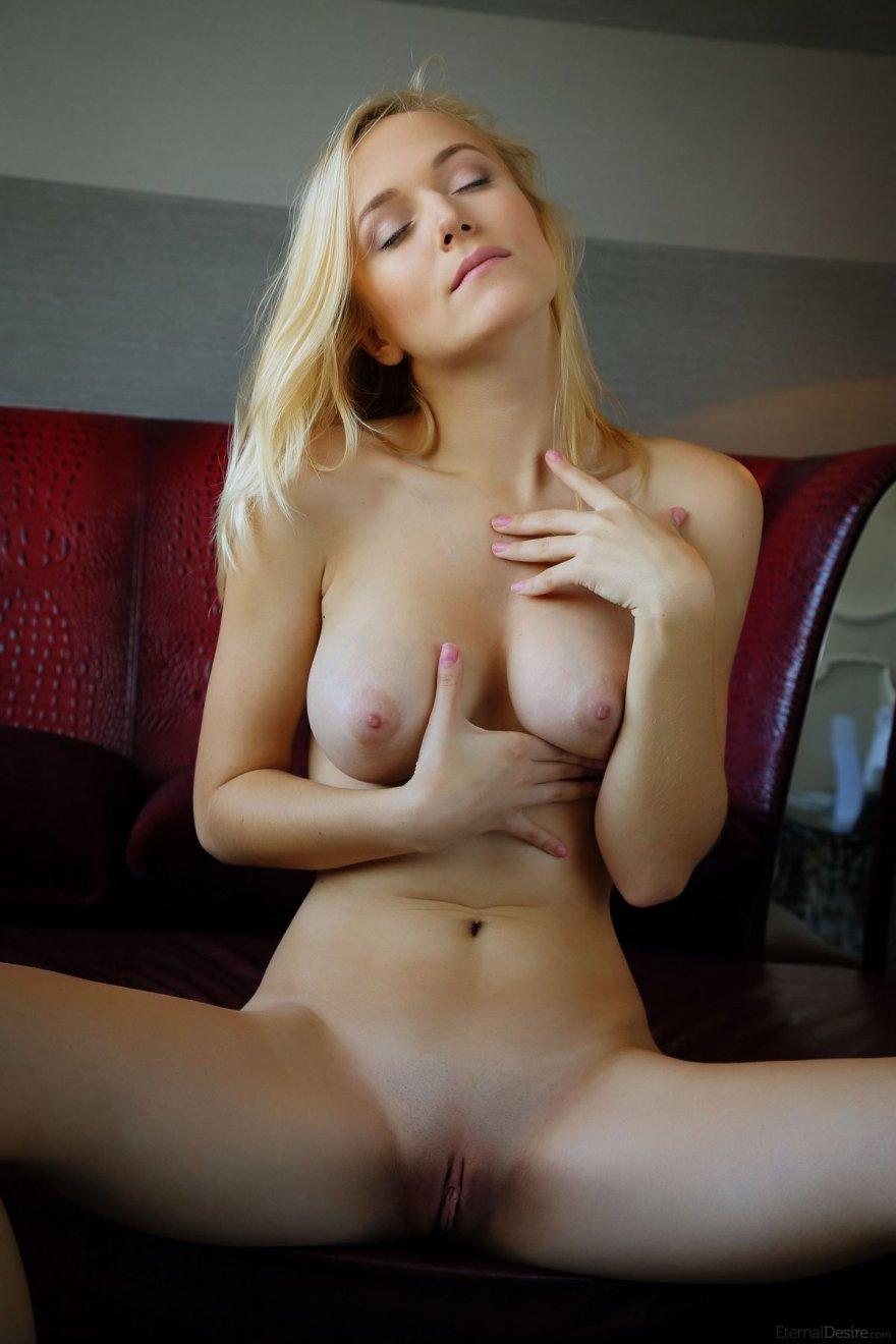 Нежная девушка красиво позирует на кожаном диване