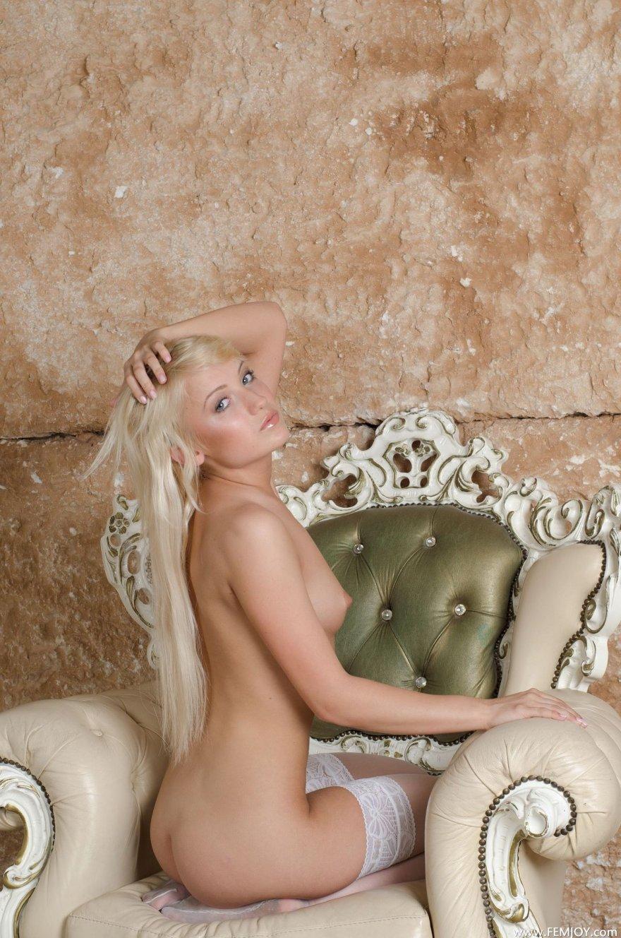 Голая блондинка в белых чулках позирует в кресле
