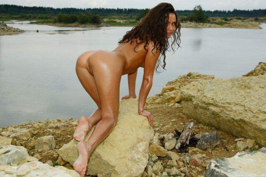Темноволосая девка с загорелым туловищем на каменистом берегу секс фото