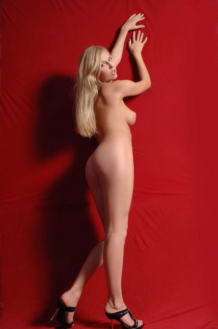 Раздетая модель со свелыми волосами на красном фоне