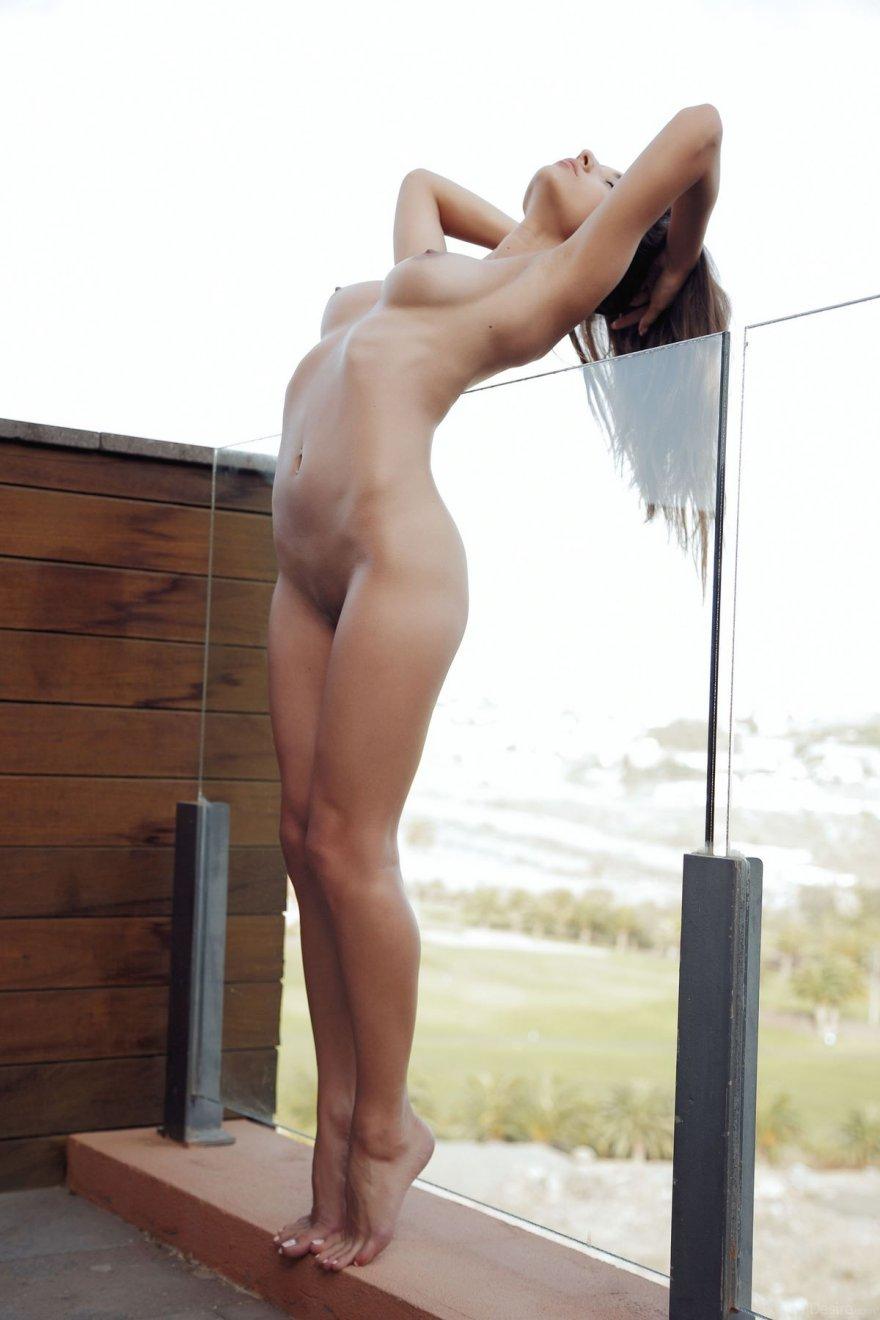 Обнаженная шатенка на стеклянном балконе