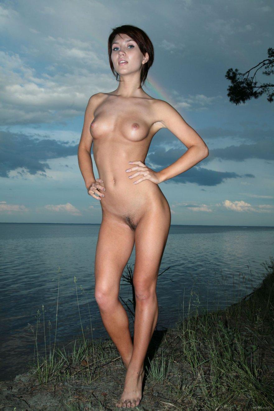 Обнаженная девушка вечером на берегу реки