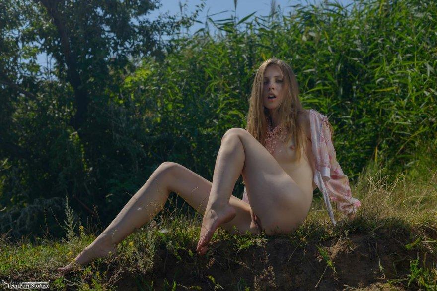 Девушка в мокрой кофточке позирует на природе