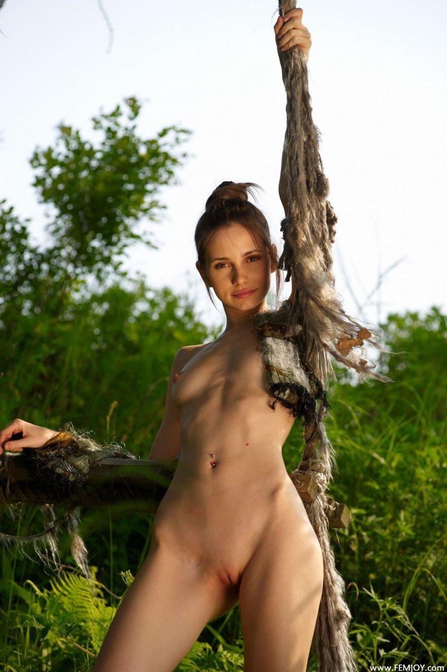 Худенькая голая девушка на качелях