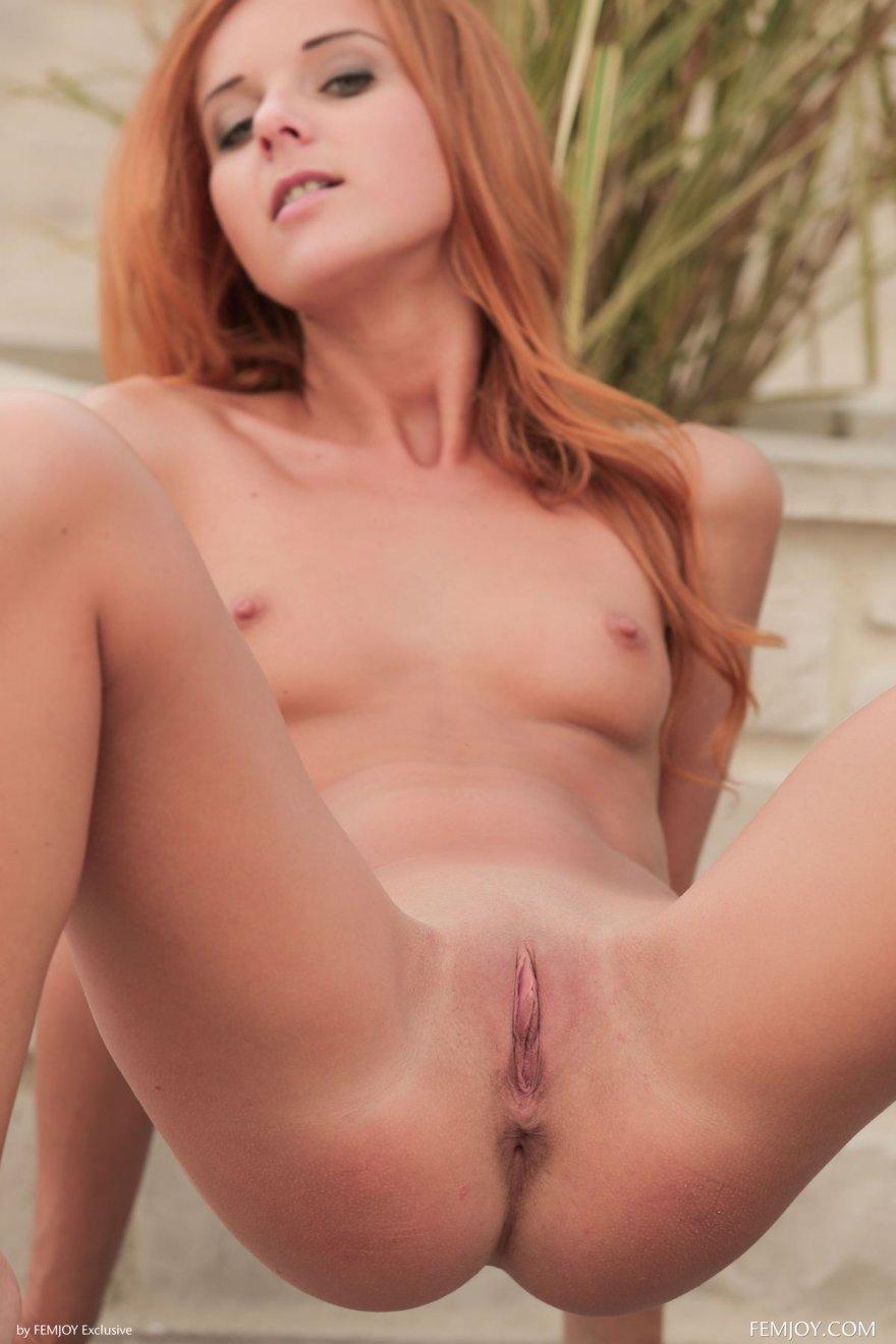 Стройная рыжая девушка в черном купальнике