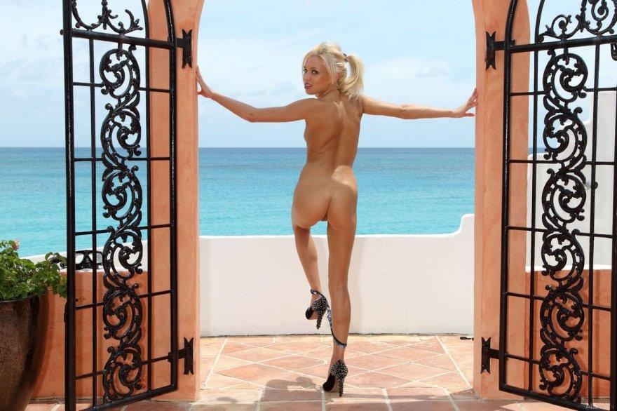 Красивая загорелая девушка откровенно позирует на балконе