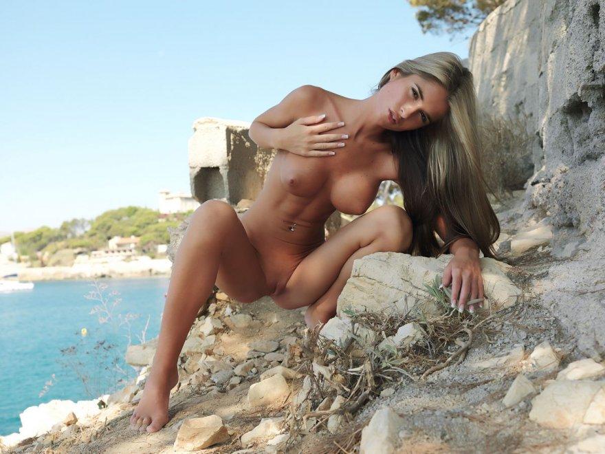 Великолепная woman раздетая на каменистом берегу