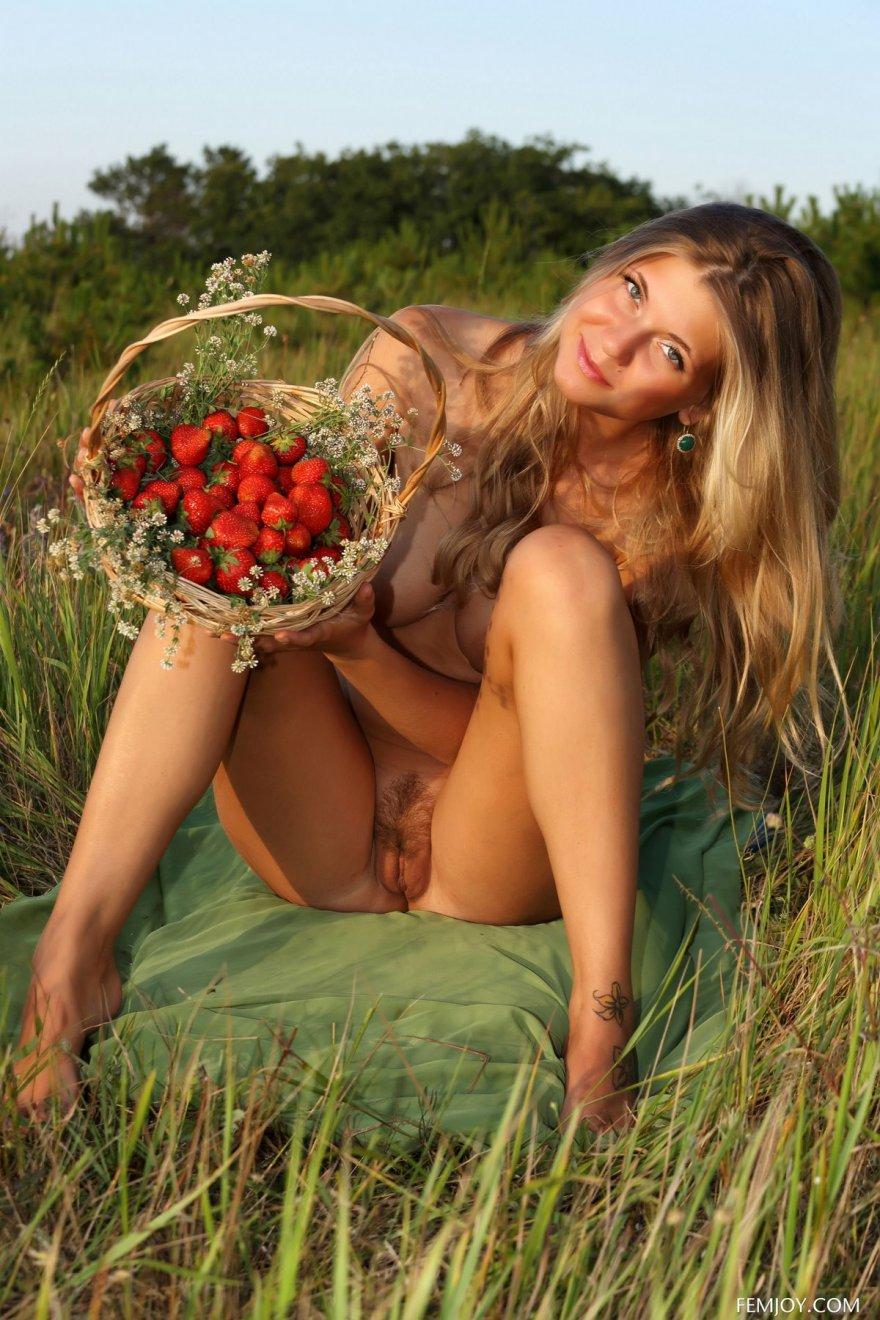 Красивая обнаженная девушка с клубникой на лугу