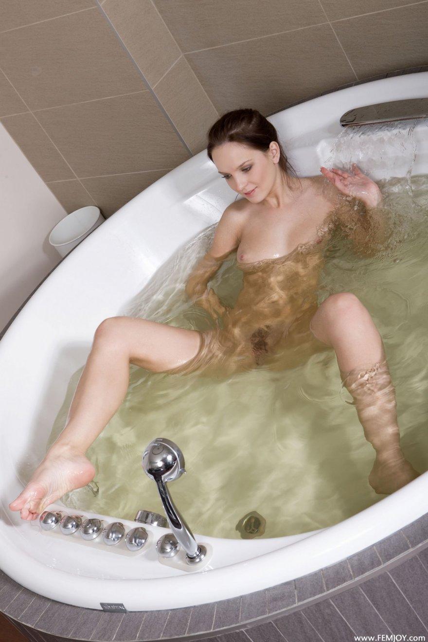 Изящная голая девушка в круглой ванне
