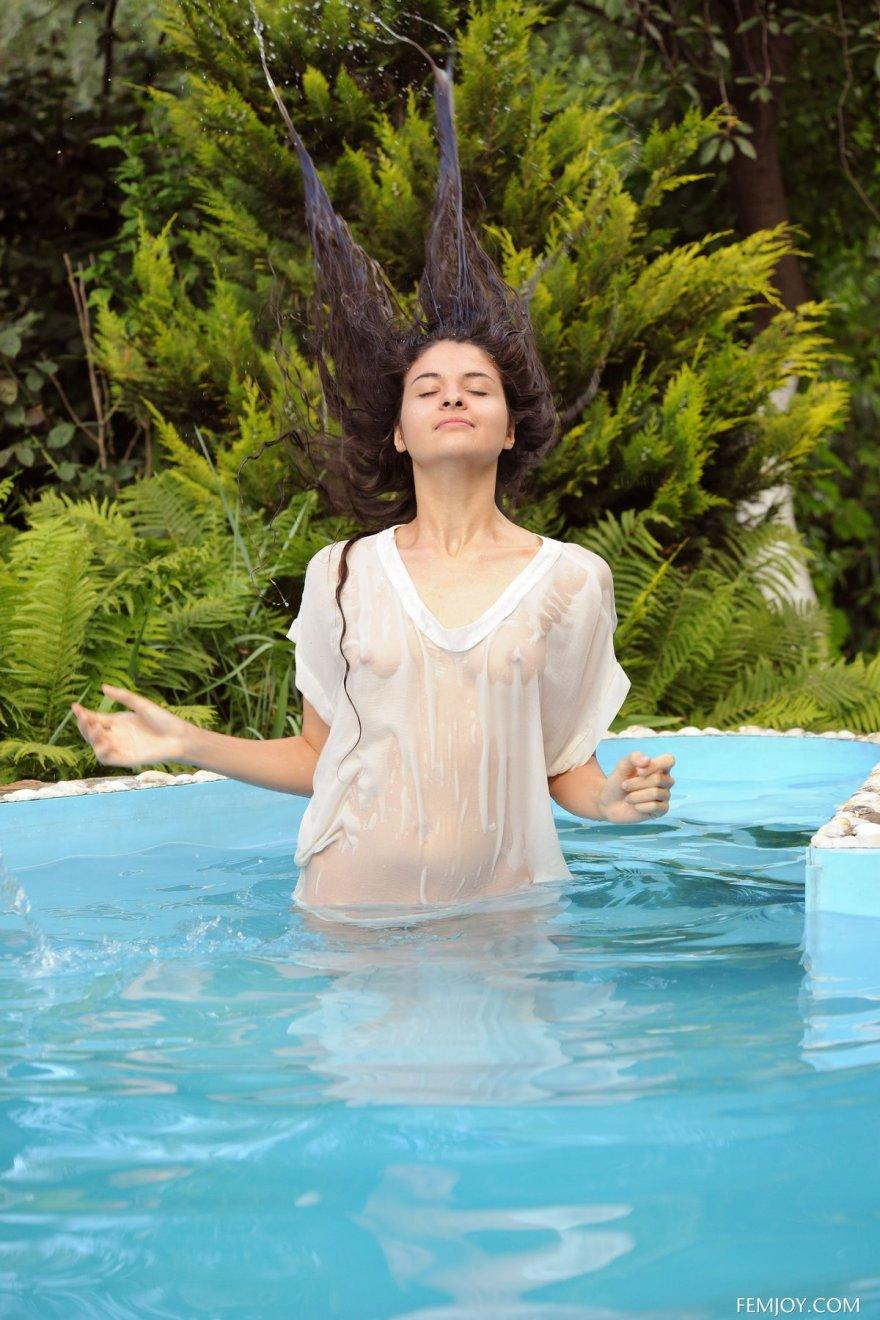Брюнетка с длинными волосами купается в бассейне