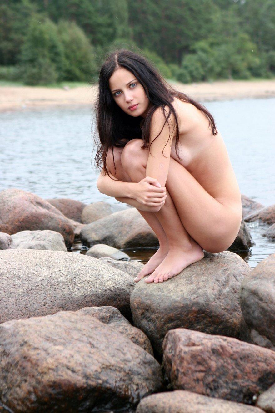 Стройная раздетая темненькая девушка около реки