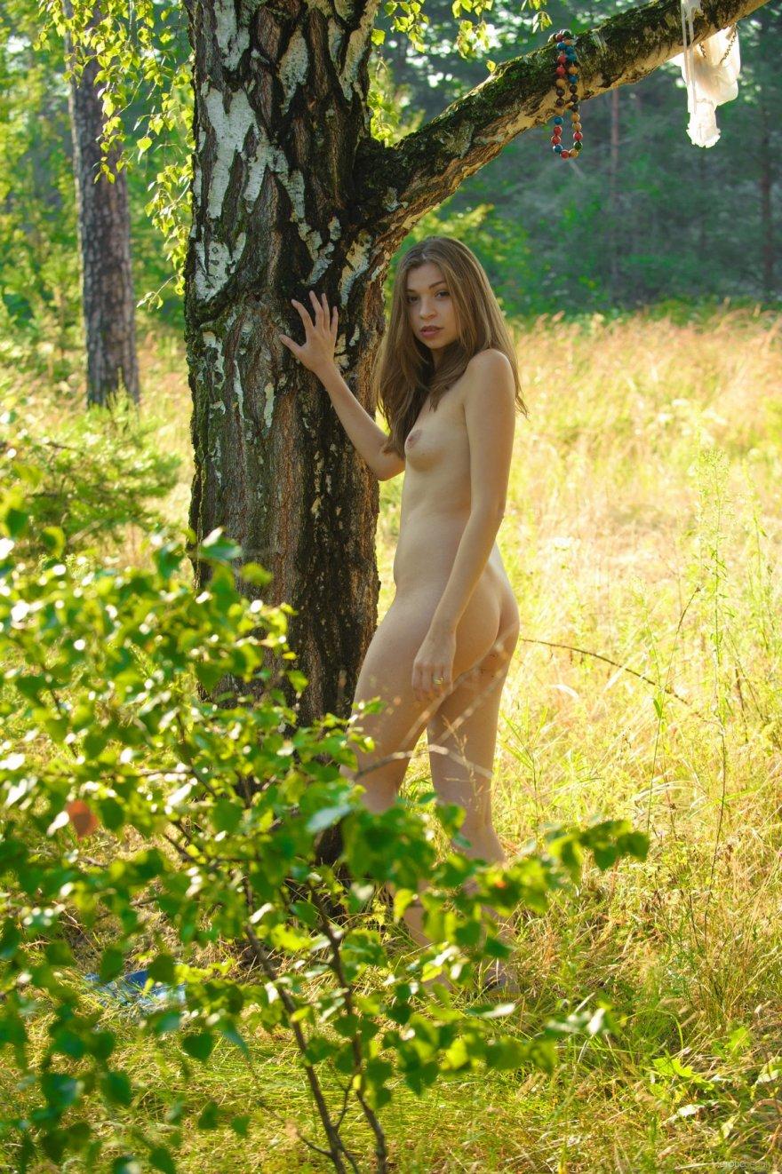 Молодая девка с татухой на животе обнаженная под деревом