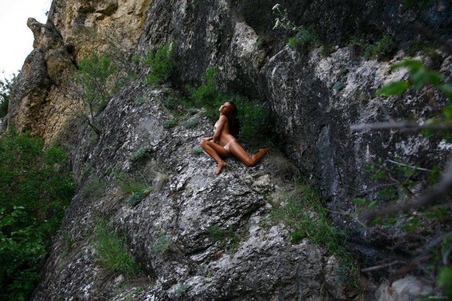 Смуглое тело шатенки на скале