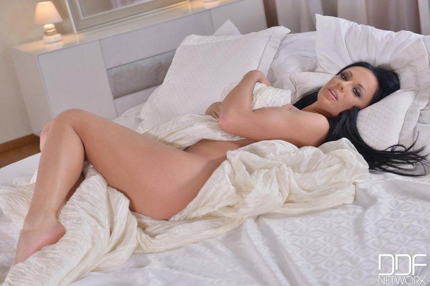 Сексуальная брюнетка с длинными волосами в спальне