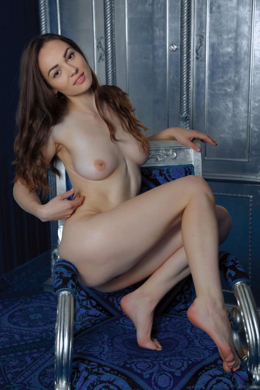Молодая голая девушка в синей комнате