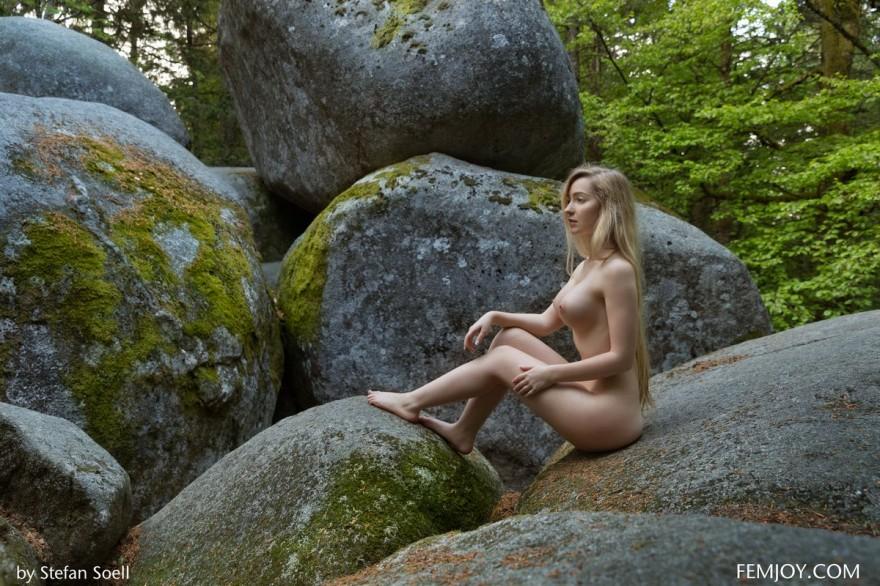 Фото ню девушки с длинными волосами на огромных камнях