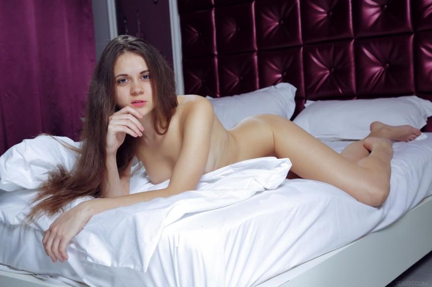Обнаженная совершеннолетняя девка с длинными волосами на лежанке