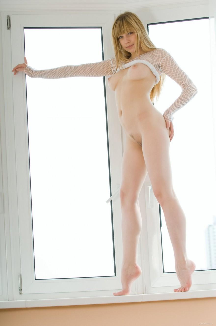 Девушка в платье-сетке и белых чулочках возле окна