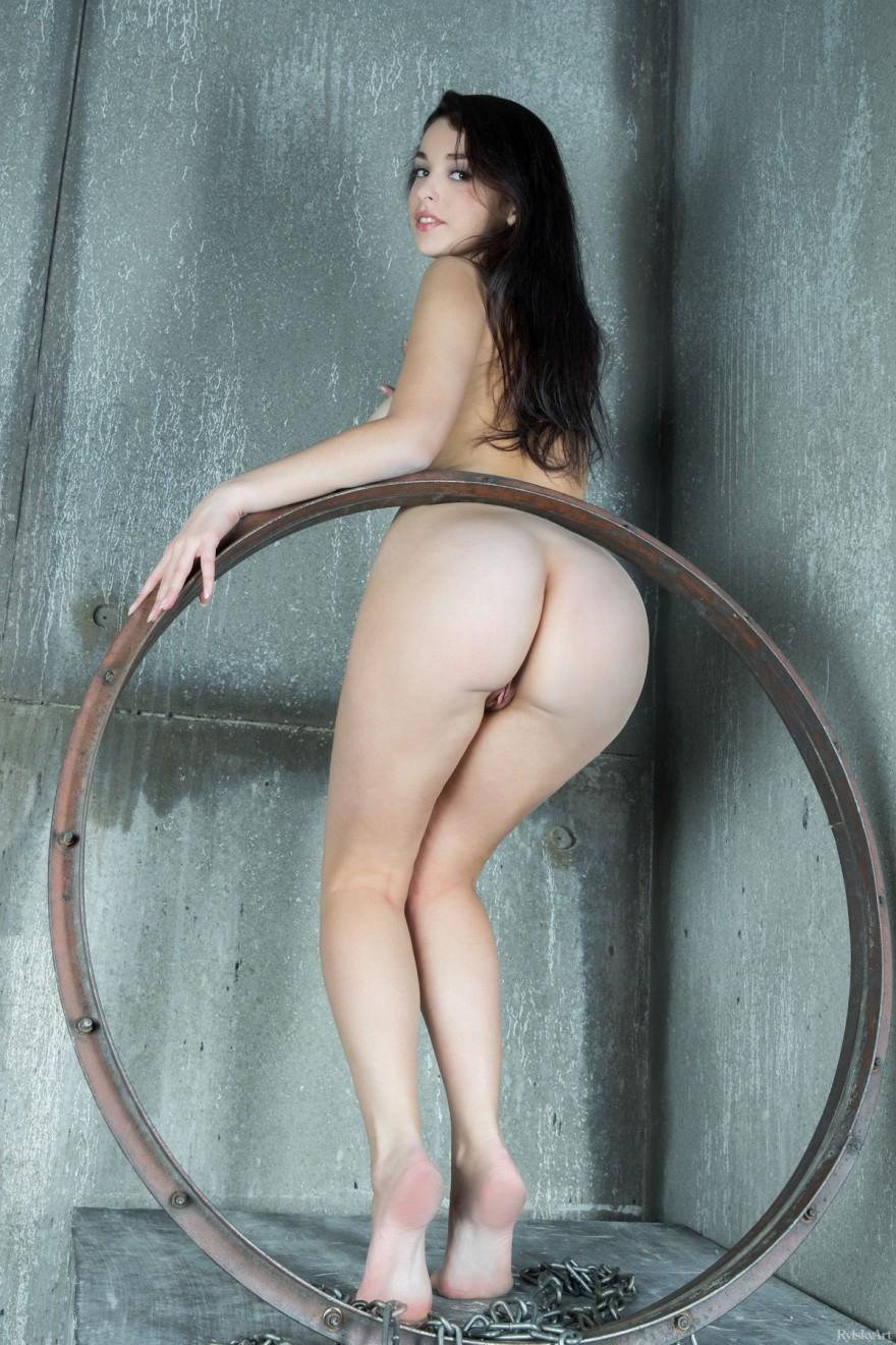 Обнаженная темноволосая девка с симпатичными дойками в цепях