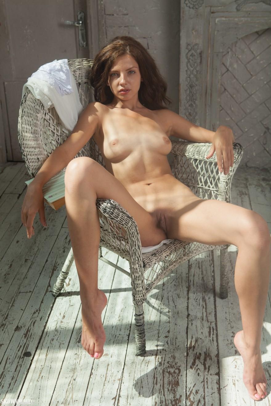 Обнаженная шатенка в плетеном кресле