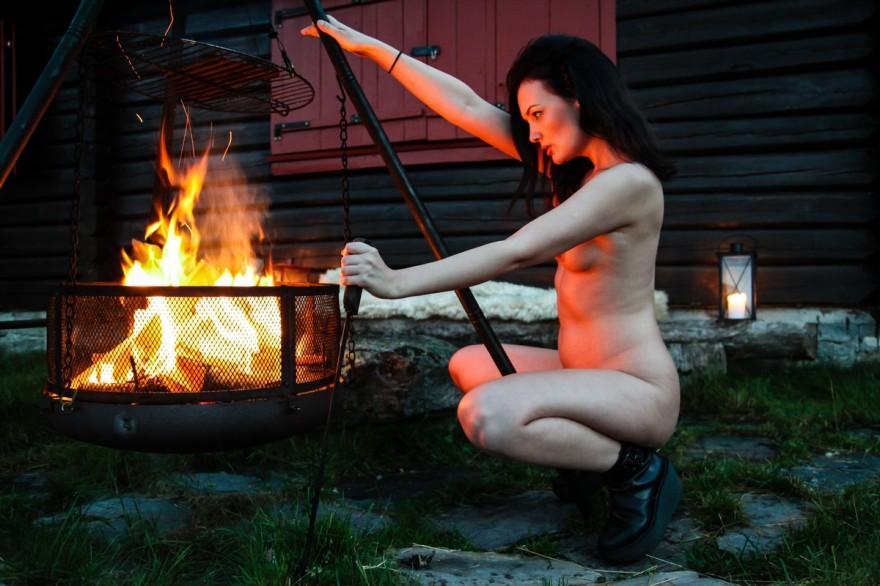 Голая девушка греется возле костра