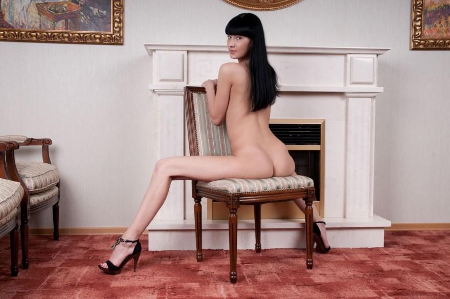 Девушка с интимным пирсингом на фоне камина