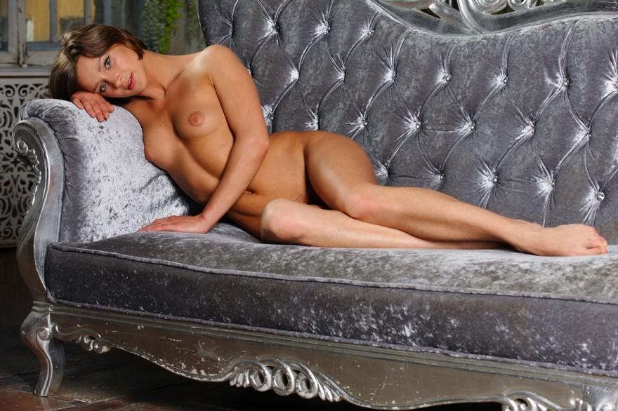 Обнаженная темноволосая девка на серебристом диване