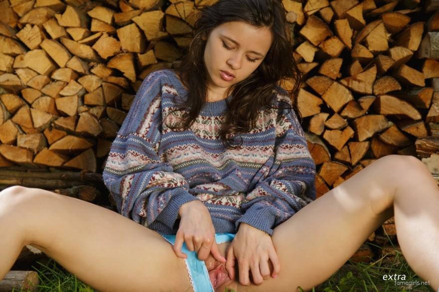 Девушка в голубых трусиках возле поленницы