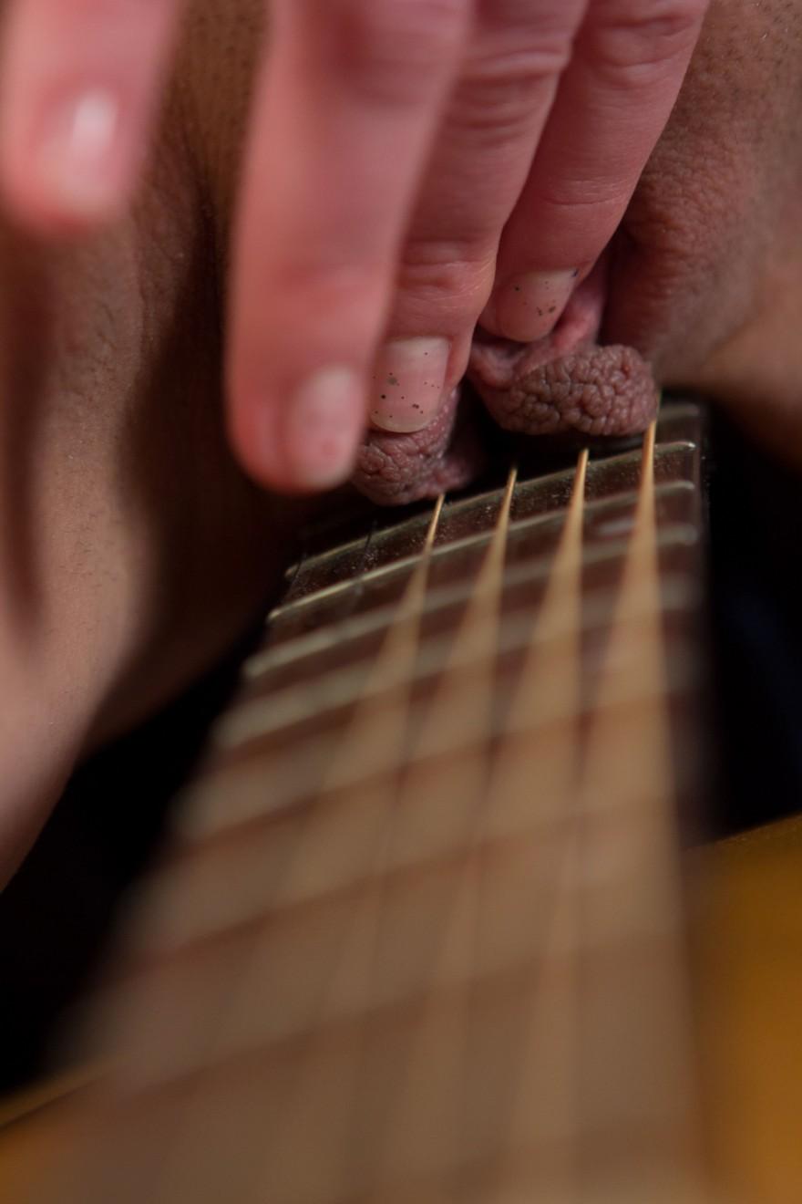 Девушка с гитарой ласкает влажную киску