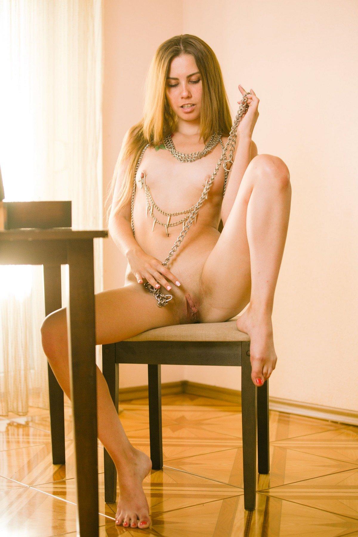 Раздетая модель со свелыми волосами украсила сосочки цепочкой