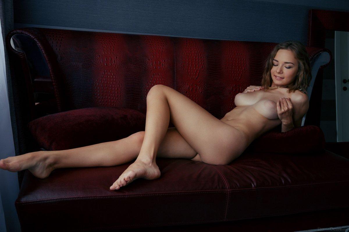 Молодая девушка откровенно позирует на кожаном диване