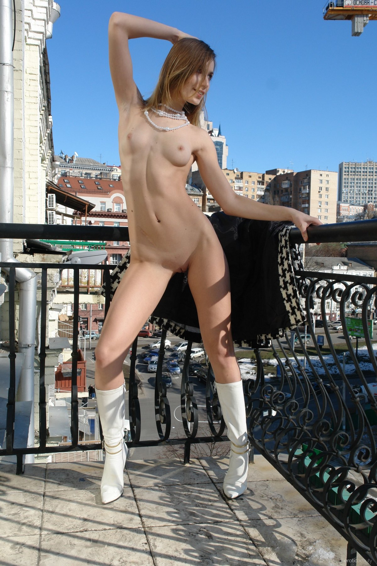 Девушка голая в белых сапожках на балконе