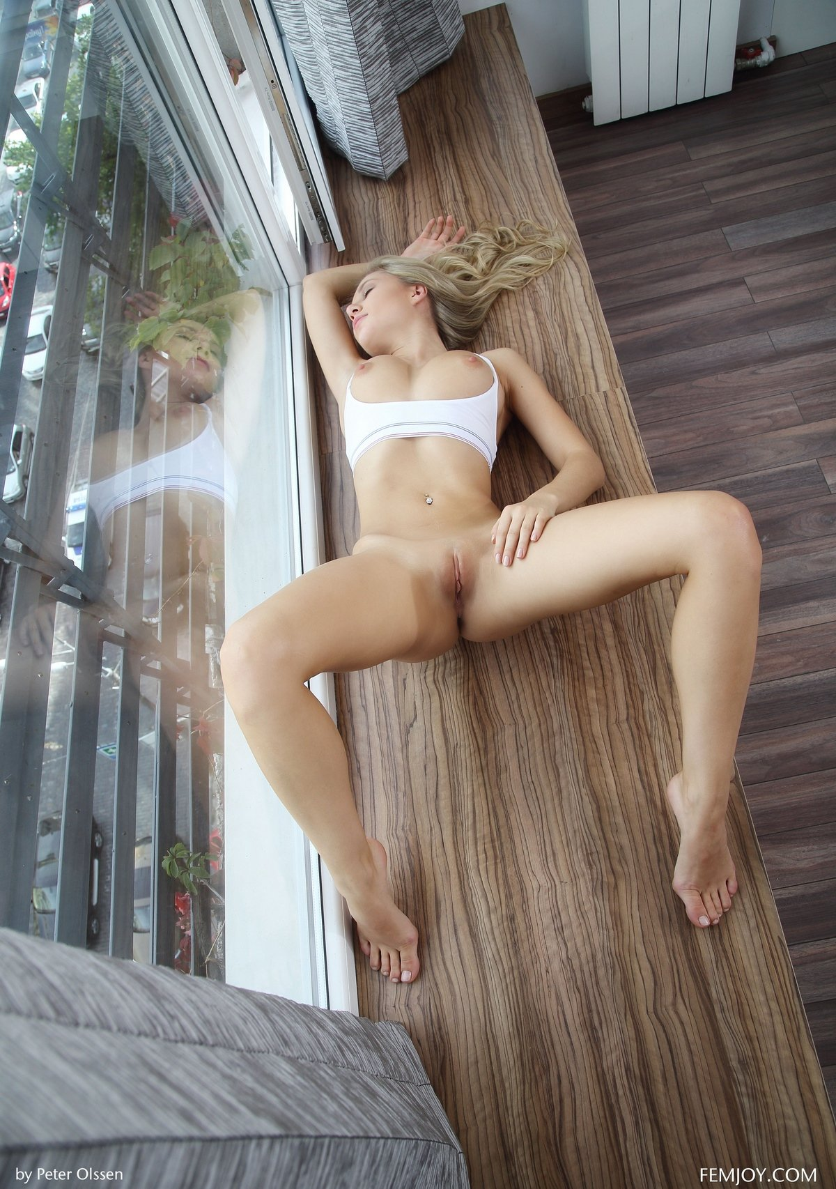 Блондинка с красивым телом возле большого окна