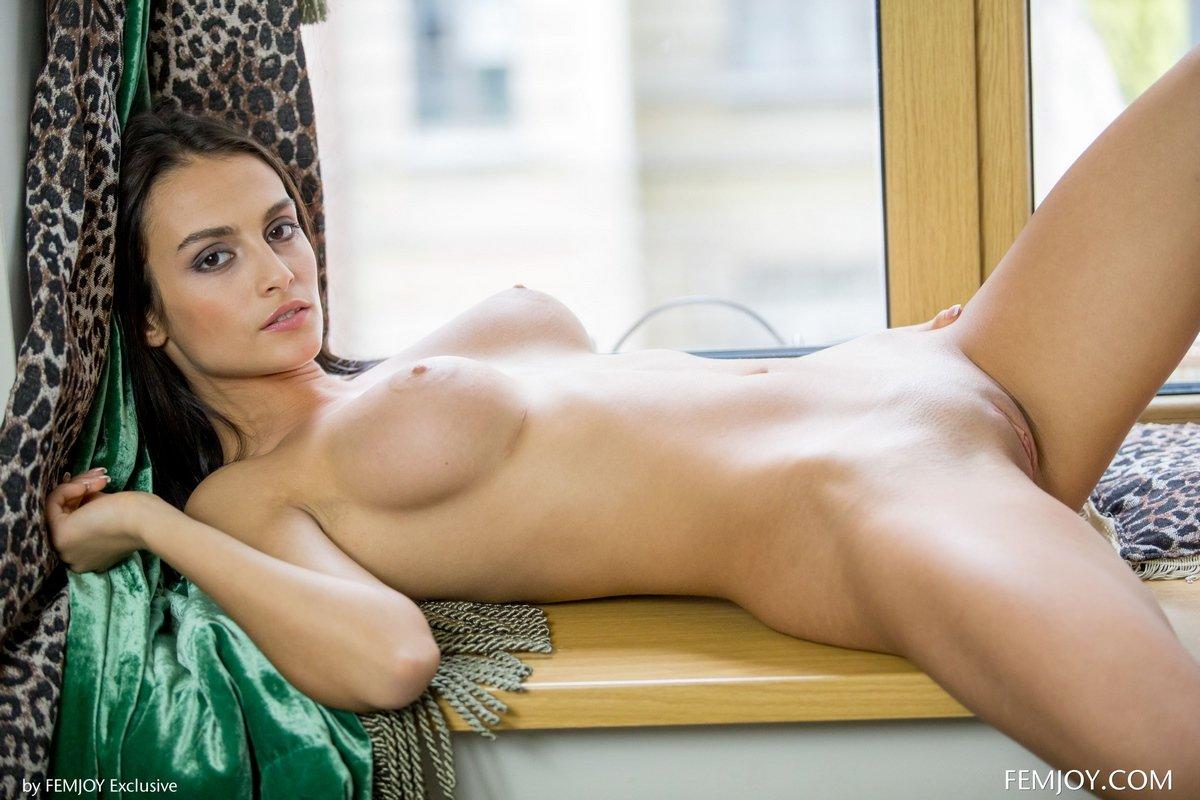 Красивая брюнетка обнаженная на подоконнике
