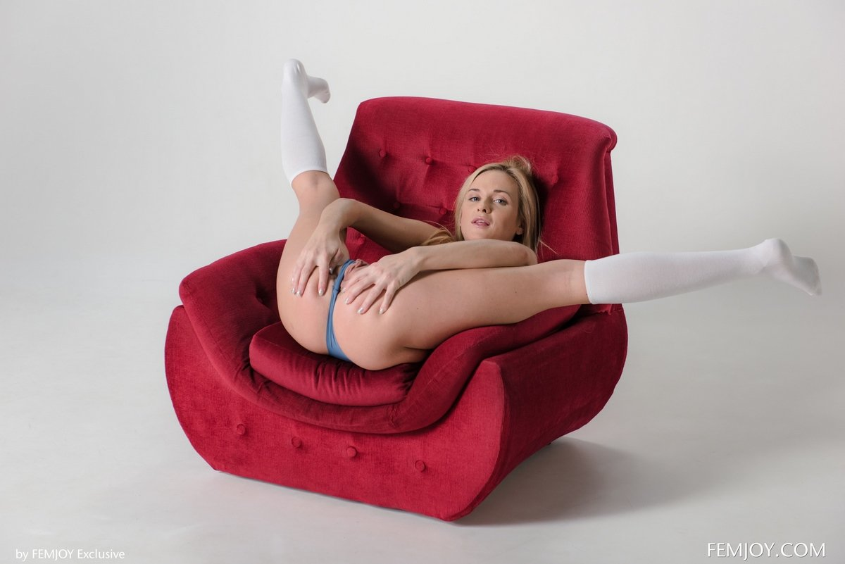 Голая блондинка широко раздвигает ножки в красном кресле