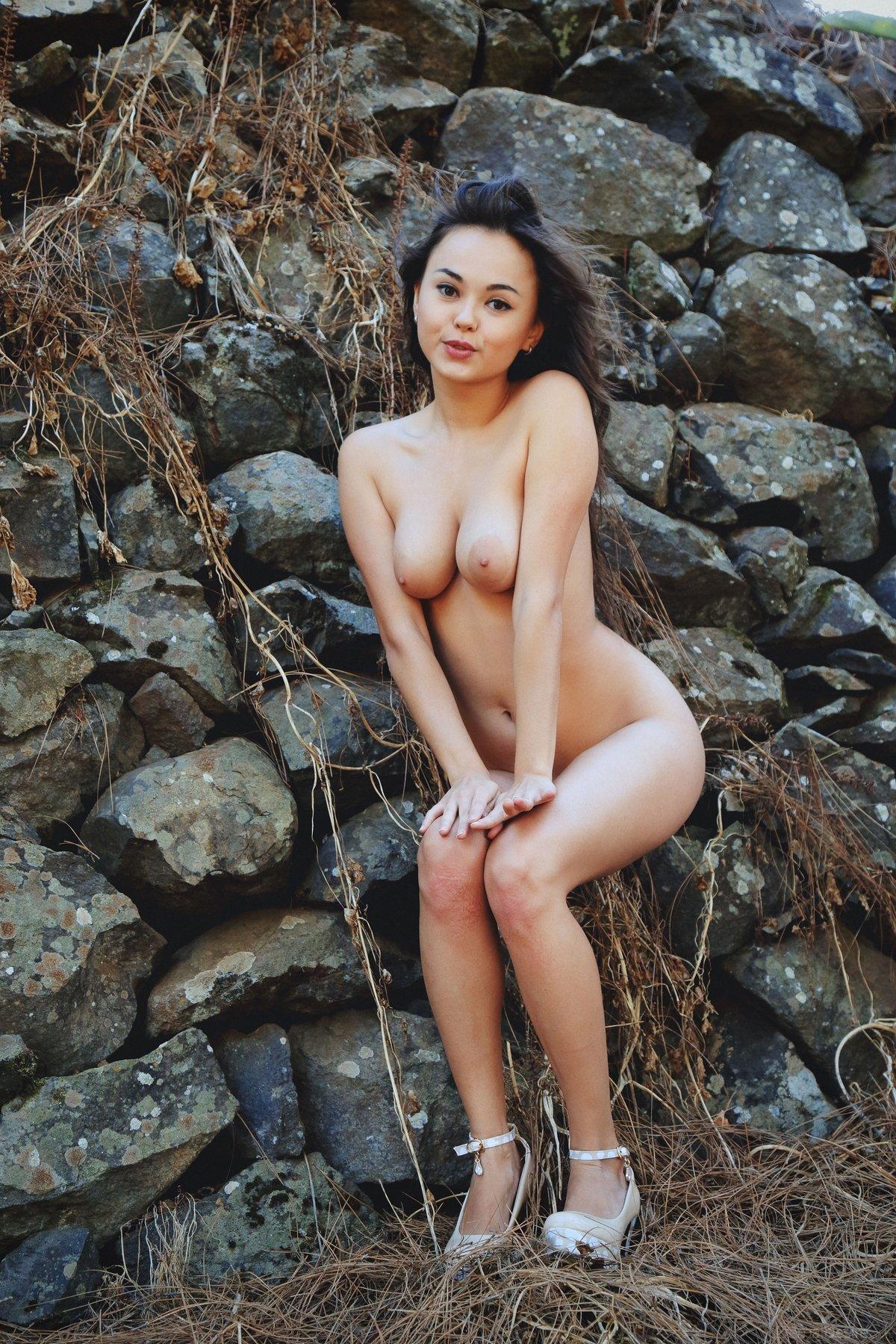 Роскошная обнаженная темненькая девушка возле каменной стены