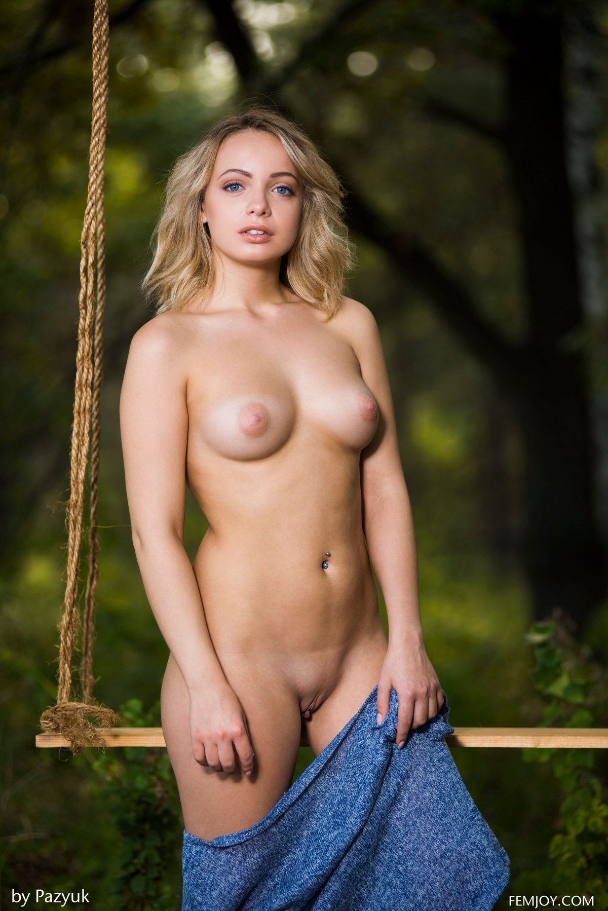 Блондиночка с светло-синими глазами ню модели на качелях