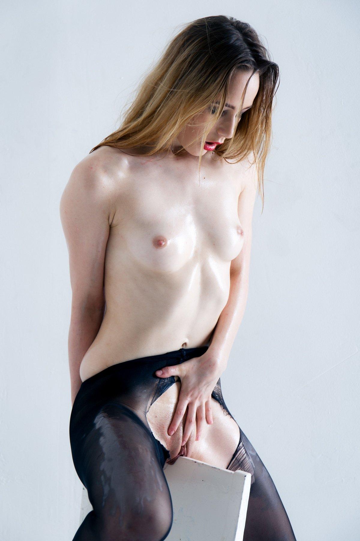Блондинка в рваных колготках на голое тело