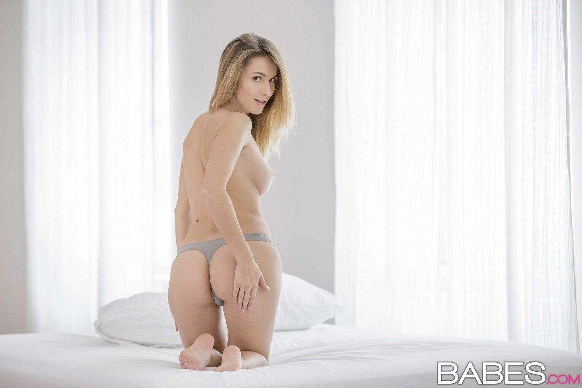 Светлая порноактриса снимает нижнее белье в кровати