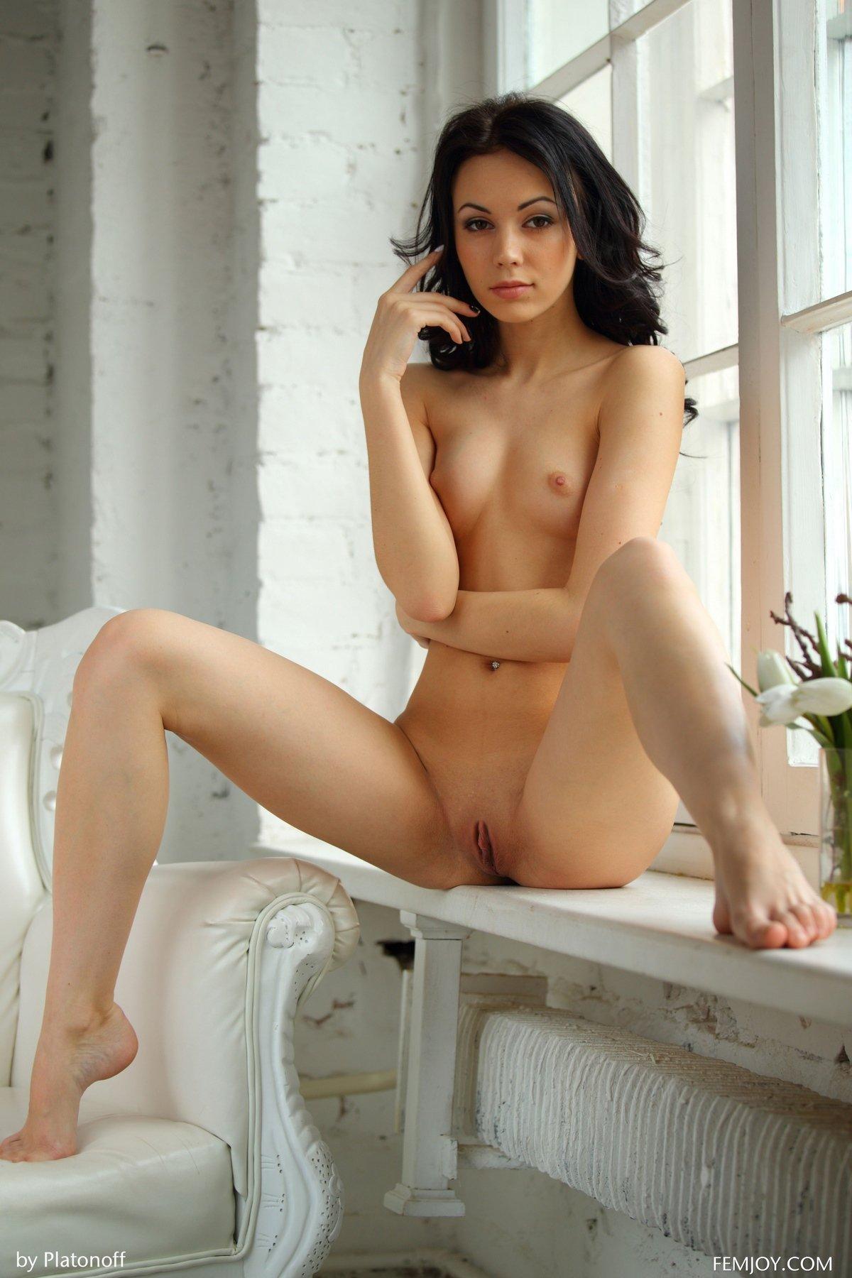 Красивая голая брюнетка в кресле у окна