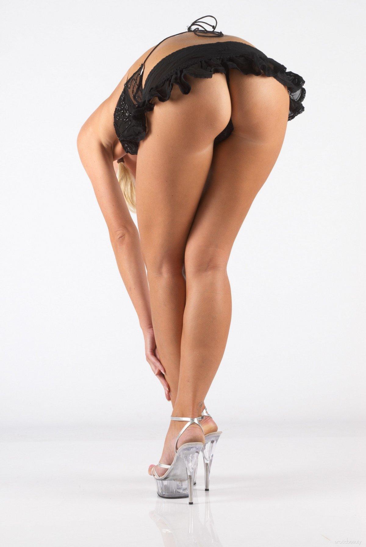 Модель в эротичном наряде позирует в студии
