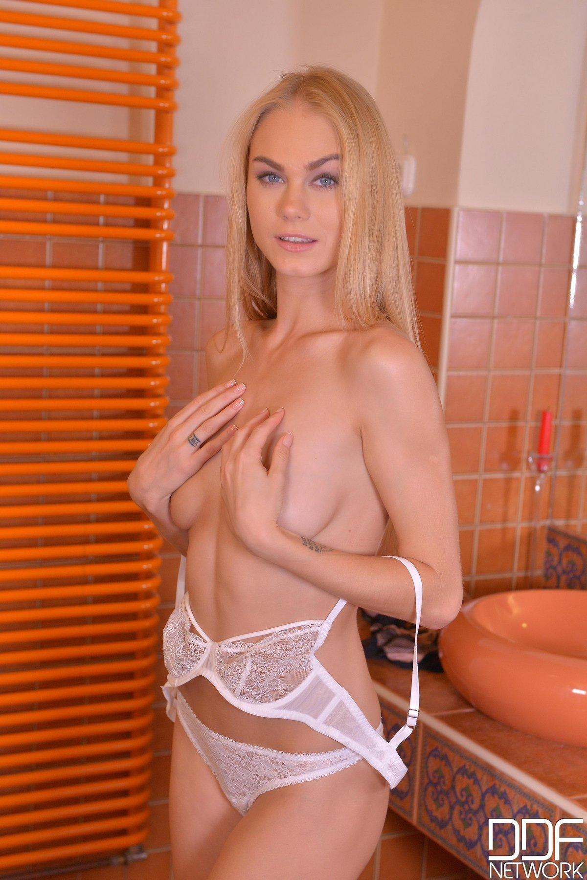 Модель со свелыми волосами в кружевном белье позирует в спальне секс фото