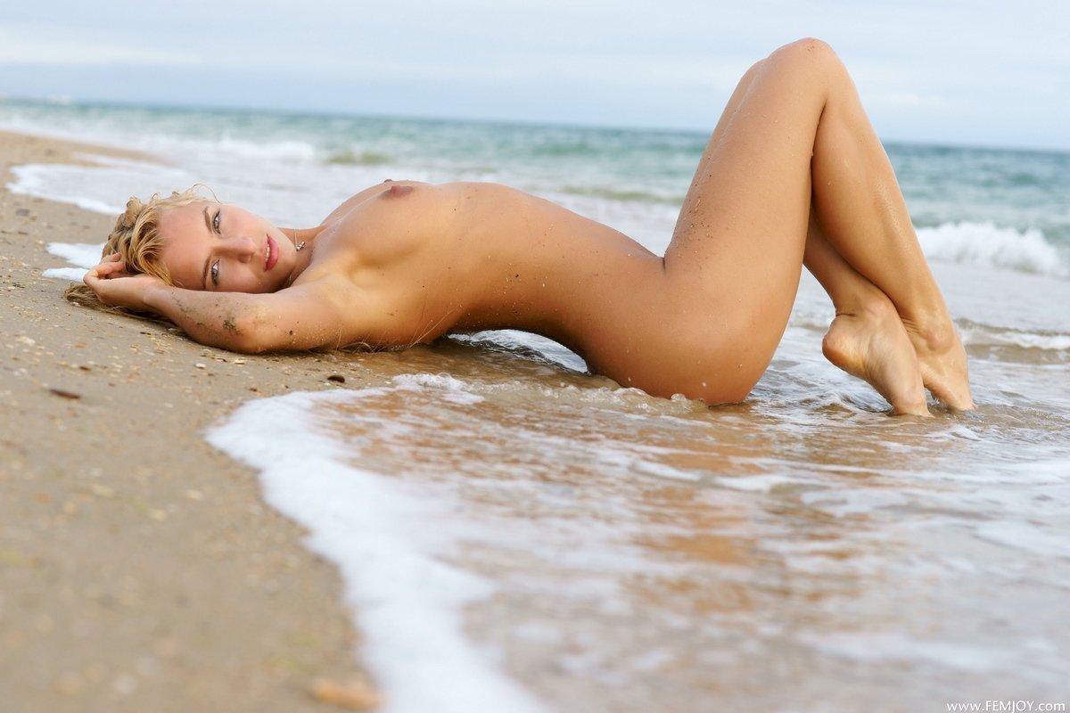 Обнаженная блондинка купается в море
