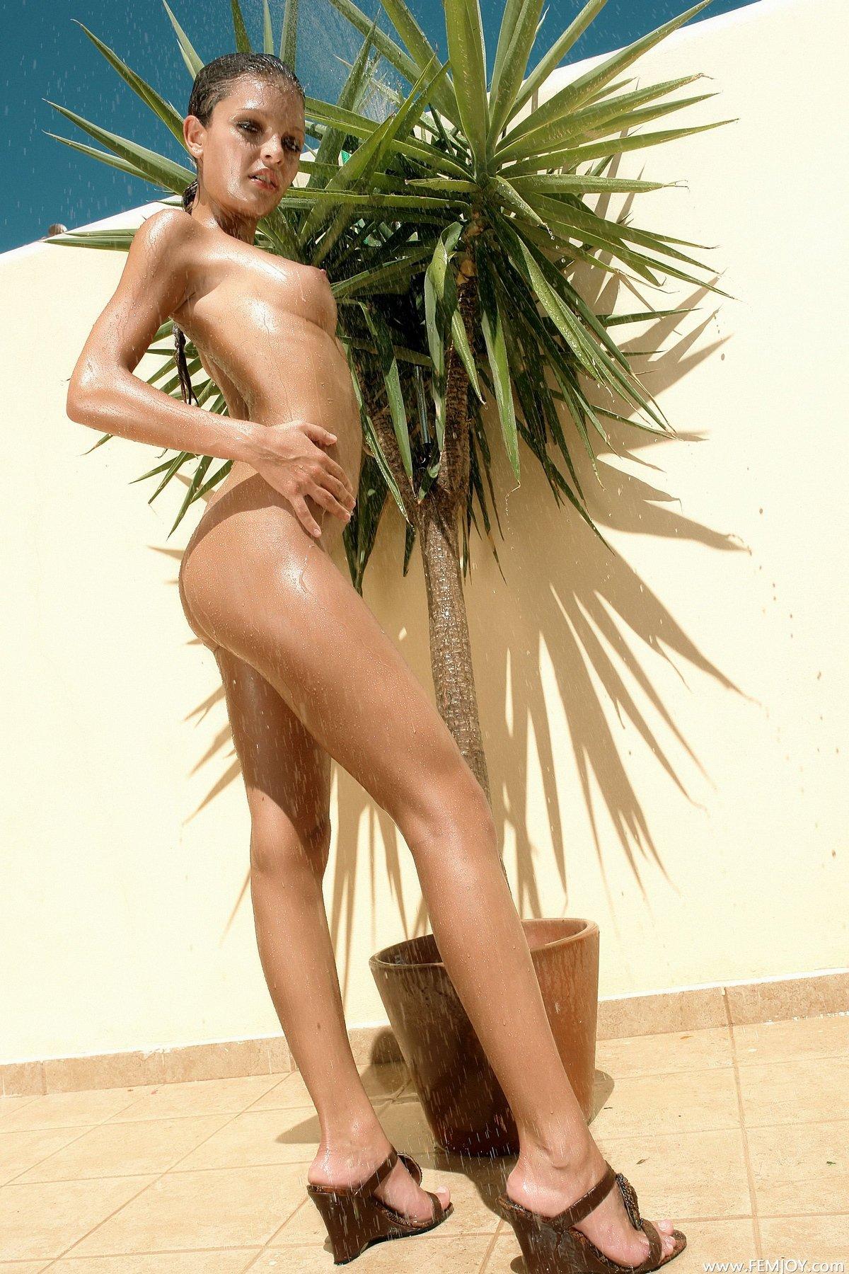 Фото молодой голой девушки под пальмой