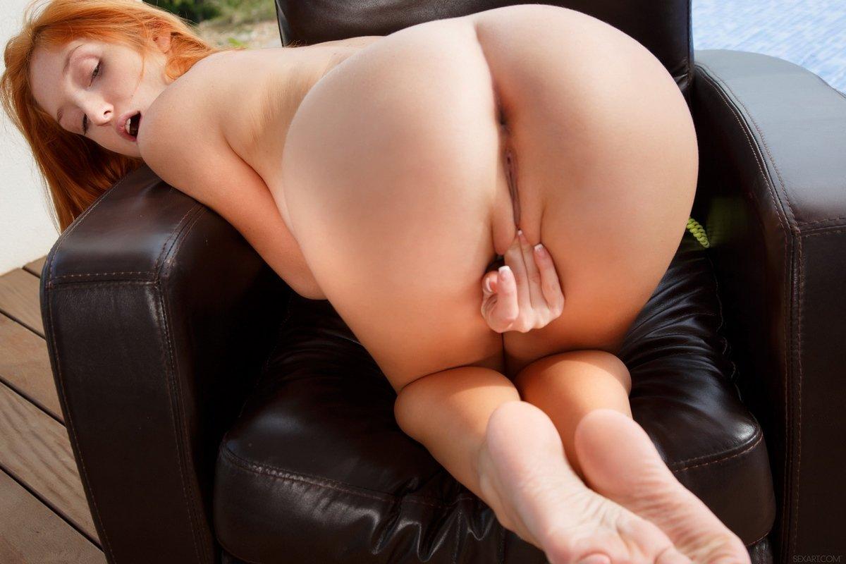 Сексуальная рыжая девушка голая в кожаном кресле