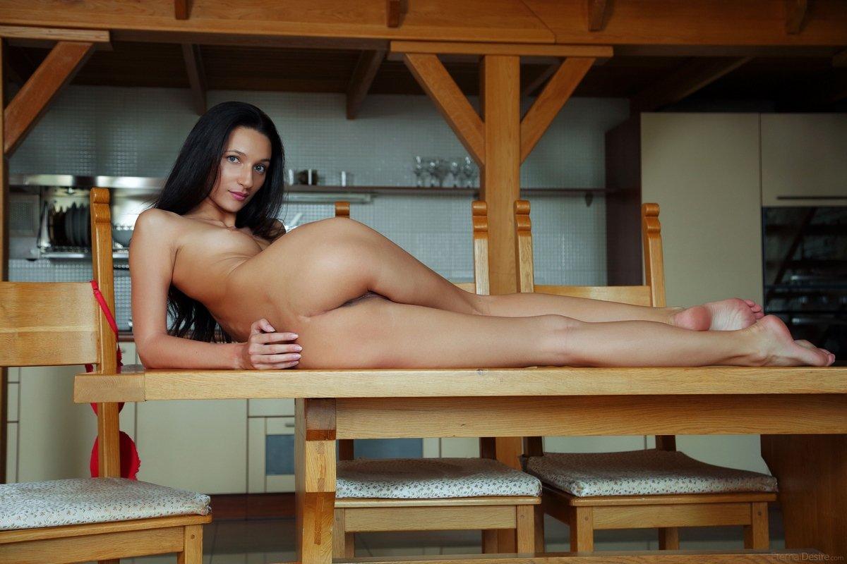 Раздетая темноволосая девка на гигантском деревянном столе