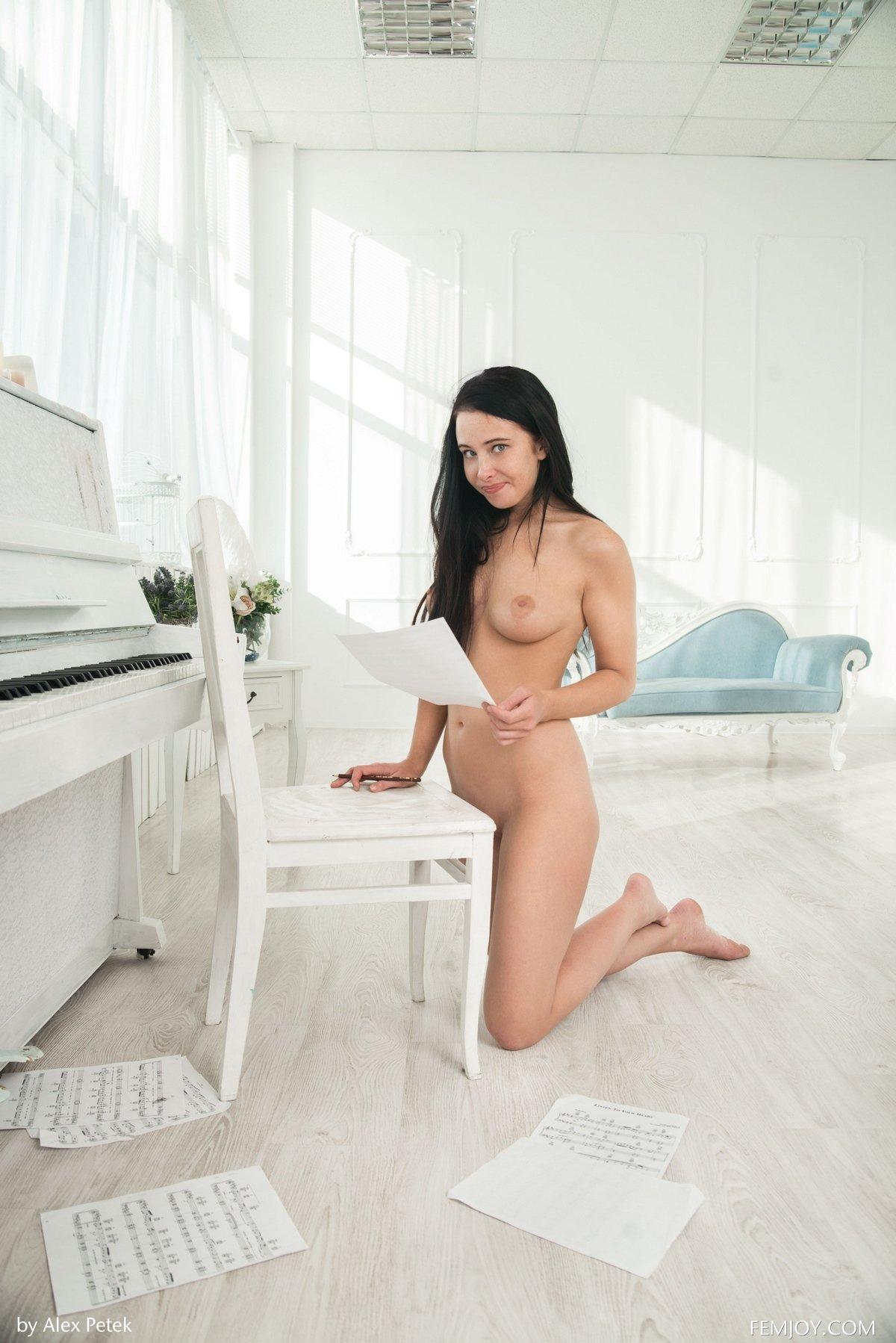 Обнаженная темненькая девушка возле светлого рояля