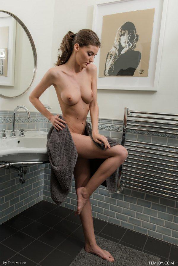 девушка в мокрой рубашке возле камня фото